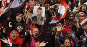 Il volto di Mohammed Morsi obliterato nei cartelli della protesta di Piazza Tahrir.